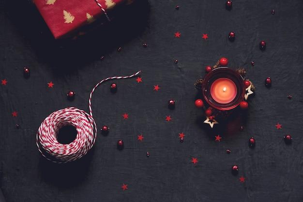 Sfondo nero festivo con decorazione rossa, candela e regalo, chrtistmas e biglietto di auguri di capodanno con posto per il testo