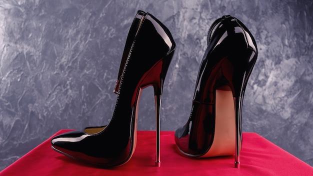 Tacchi alti a spillo in vernice lucida nera fetish con cinturino alla caviglia