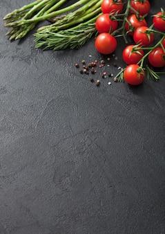 Sfondo di cibo nero con asparagi, pomodorini e rosmarino sul fondo della tavola nera con pepe nero.