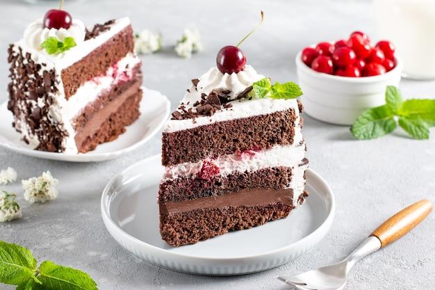 Torta della foresta nera decorata con panna montata e ciliegie su un tavolo di cemento chiaro, fetta di torta. torta di natale