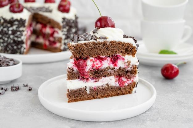 Torta foresta nera, torta schwarzwald. torta al cioccolato fondente, panna montata e ciliegia su fondo grigio cemento. copia spazio.