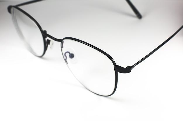 Occhiali con montatura nera su sfondo bianco. foto ravvicinata.