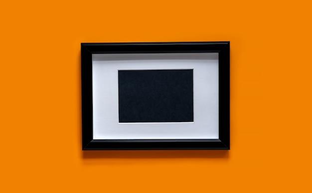 Cornice nera su sfondo arancione. vista piana laico e dall'alto.