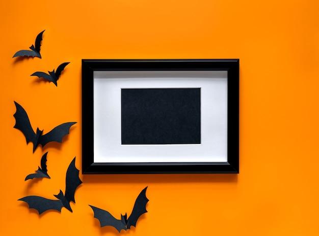 Cornice nera con pipistrelli su sfondo arancione. vista piana laico e dall'alto.