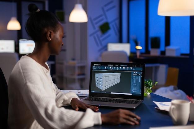 Architetto freelance nero che lavora in un software 3d per elaborare il design del contenitore seduto alla scrivania in ufficio a mezzanotte