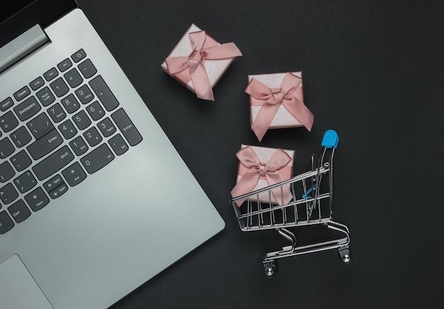 Composizione venerdì nero. acquisti online. laptop e scatole regalo con fiocchi su sfondo nero. vista dall'alto