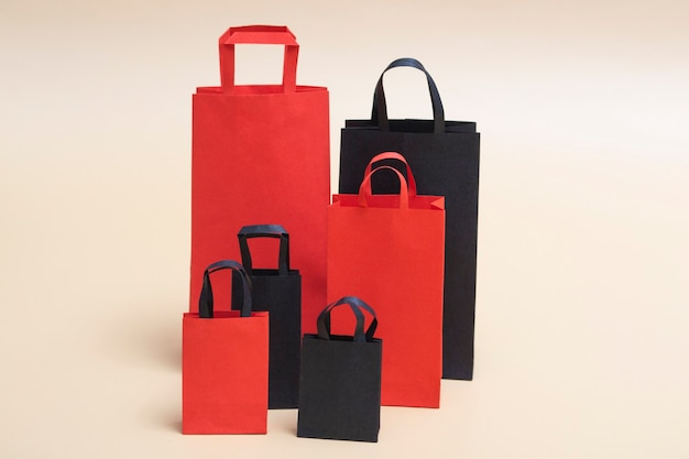 Concetto di black friday, mockup di pacchetti di carta neri e rossi su sfondo colorato. saldi del black friday