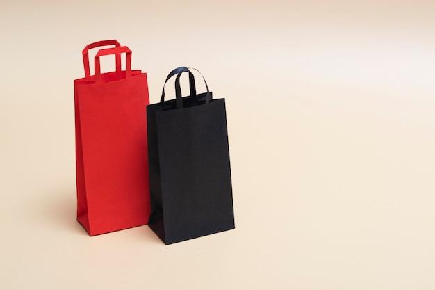Concetto di black friday, mockup di pacchetti di carta neri e rossi su sfondo colorato. venerdì nero. con copia spazio