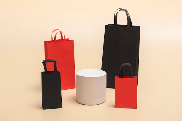 Concetto di black friday, mockup di borse della spesa di carta nere e rosse su podio bianco su sfondo colorato. venerdì nero. con copia spazio