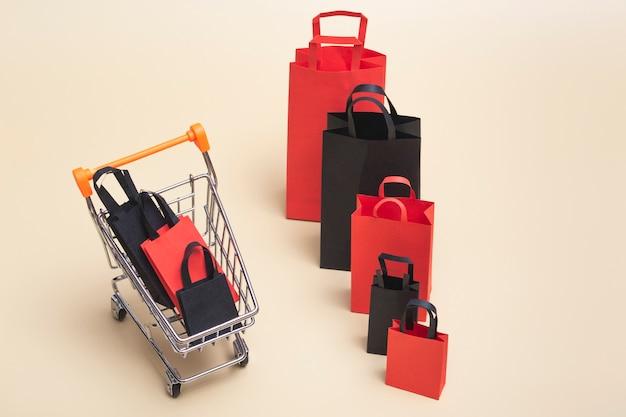 Concetto di black friday, mockup di borse della spesa di carta nere e rosse con carrello su sfondo colorato. saldi del black friday.