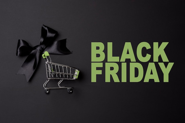 Concetto di venerdì nero con carrello della spesa su sfondo nero