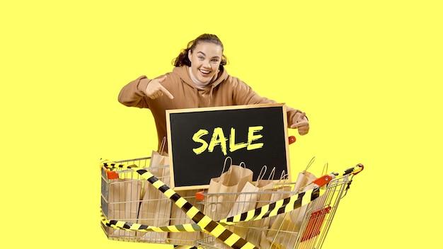 Black friday, la ragazza indica felice il cartello tra gli acquisti nel carrello