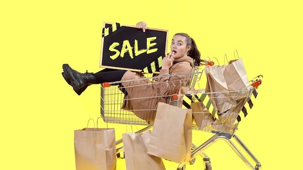 Black friday, una ragazza è seduta in un cestino della spesa e tiene in mano una tavola, guardando la telecamera sorpresa