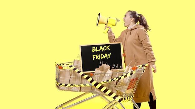 Black friday, una ragazza grida in un megafono accanto a un cartello in piedi in un carrello della spesa