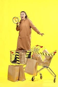 Venerdì nero. una ragazza grida in un megafono, in piedi in un cestino della spesa.