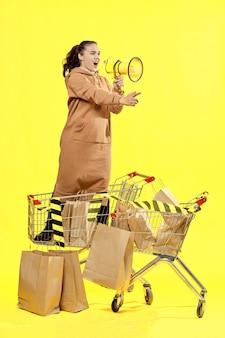 Venerdì nero. una ragazza grida in un megafono, in piedi in un carrello della spesa.