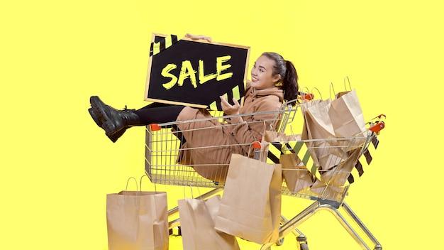 Black friday, una ragazza siede in un cestino della spesa e tiene in mano una lavagna con un posto dove copiare