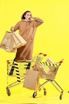 Venerdì nero. una ragazza con le borse con un'espressione sorpresa sul viso, in piedi in un carrello della spesa.