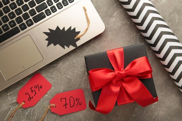 Venerdì nero. concetto di acquisto online con confezione regalo su grigio. vista dall'alto