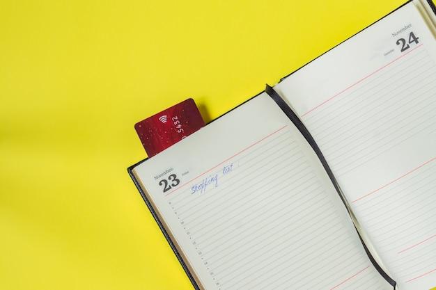 Concetto di vendita venerdì nero. lista della spesa in quaderno e carta di credito come segnalibro