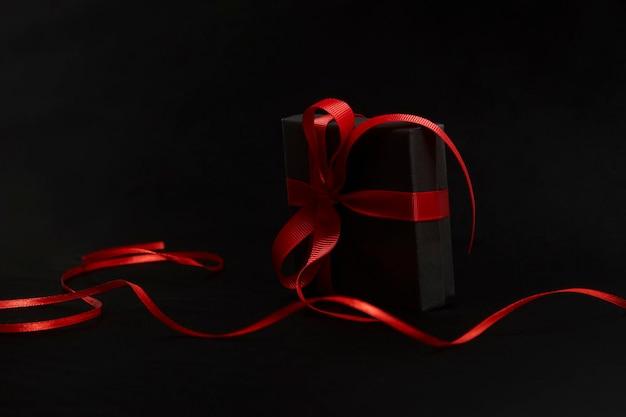 Concetto di vendita del black friday con confezione regalo con nastro, primo piano