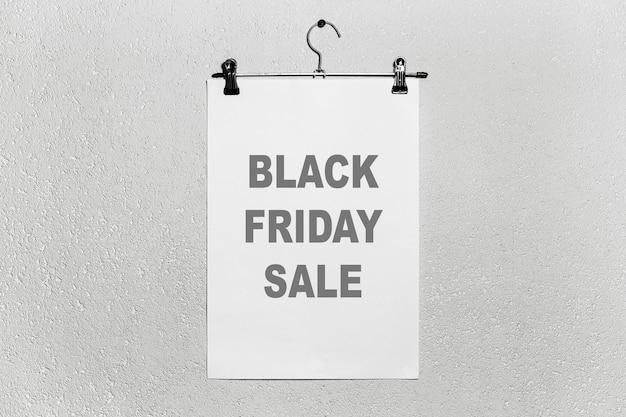 Testo di vendita venerdì nero su carta bianca, attaccato al gancio di stoffa sullo sfondo grigio con texture.