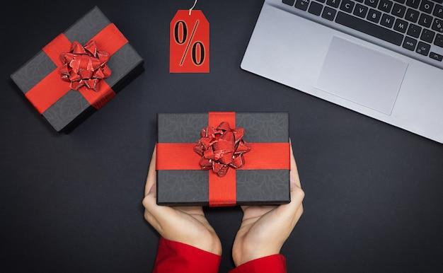 La mano della donna di vendita del black friday dà la confezione regalo su sfondo nero