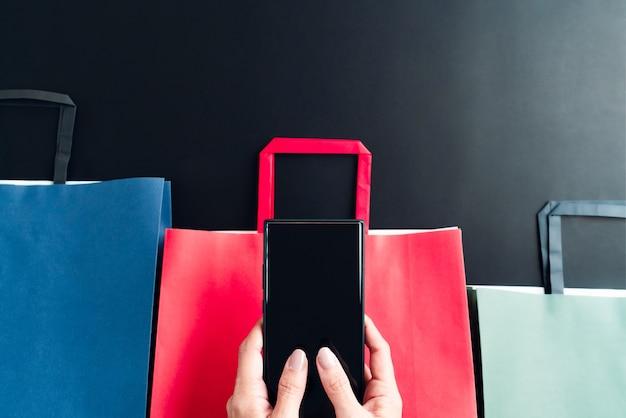 Vendita del black friday, donna mano che tiene smartphone con borsa della spesa per lo shopping online