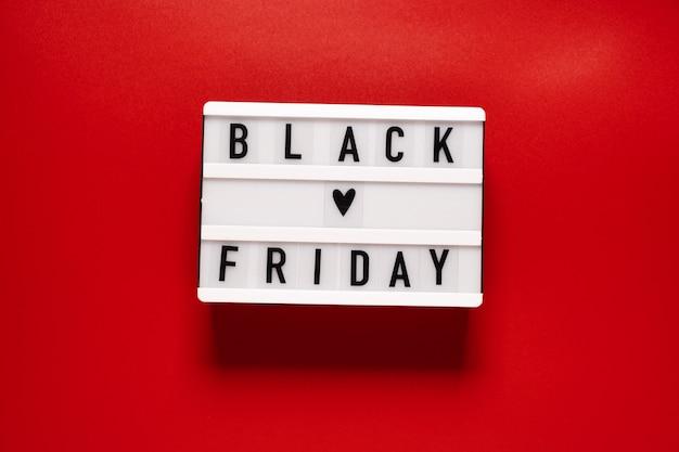 Parola di vendita del venerdì nero su lightbox su sfondo rosso