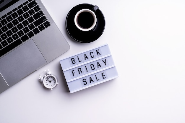 Parole di vendita del venerdì nero su lightbox con una tazza di caffè, laptop e orologio