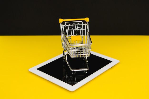 Saldi del black friday. piccolo carrello della spesa su un tablet in sfondo giallo. concetto di cybermonday