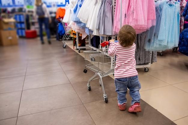 Venerdì nero shopping carino bambino stand con carrello della spesa davanti a grucce con vestiti