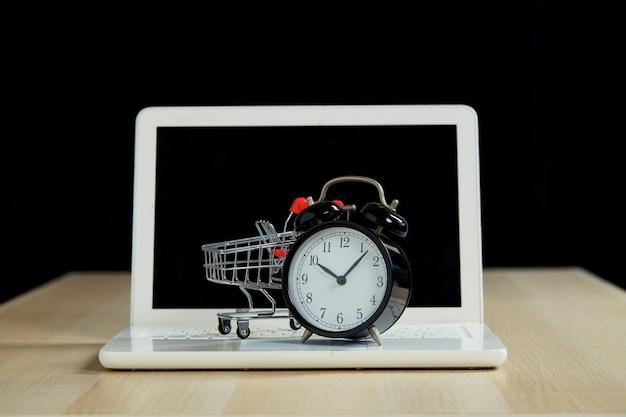 Concetto di shopping e vendita al dettaglio del black friday. computer portatile del carrello del carrello della spesa con un orologio sulla tavola di legno con un fondo nero. marketing online del supermercato o concetto di acquisto.