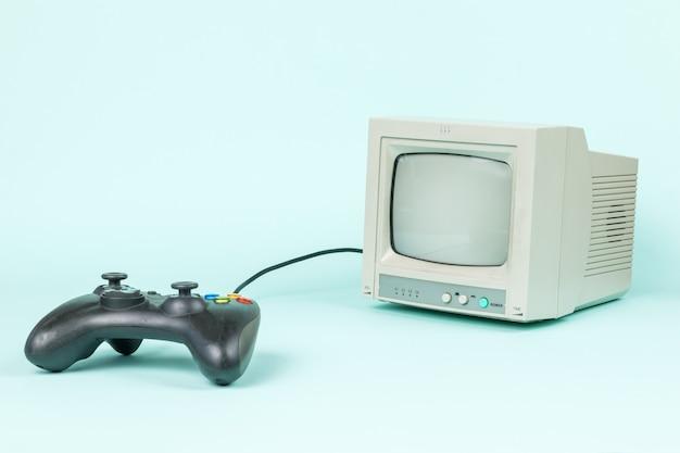 Una console di gioco nera e un monitor grigio su sfondo chiaro.