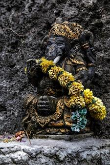 Statua nera di ganesha con una corona di fiori.