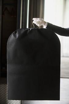 Borsa da viaggio in tuta nera per le mani di un lavoratore dell'hotel in guanti bianchi