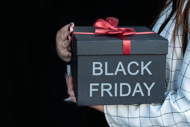Confezione regalo nera con scritta black friday. isolato su sfondo nero. ragazza con una bella confezione regalo nelle sue mani.