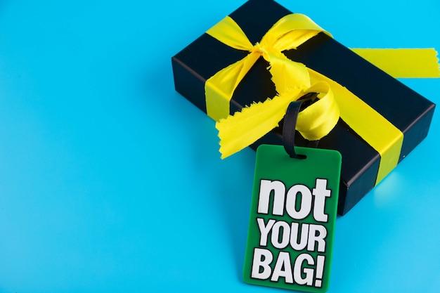 Confezione regalo nera con nastro in raso oro su fondo azzurro.