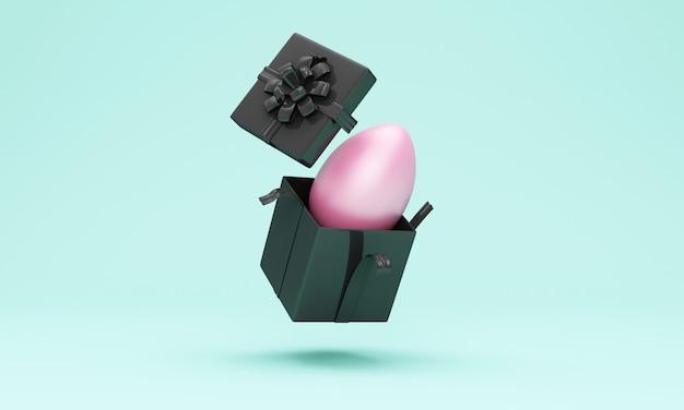 Confezione regalo nera con uovo di pasqua rosa all'interno sulla parete turchese