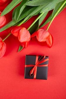Confezione regalo nera con nastro rosso vicino al tulipano rosso