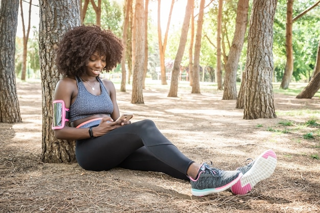 Capelli afro da ragazza nera sorridenti con vestiti da corsa seduti per terra appoggiati a un albero con smartphone in mano con alberi sullo sfondo