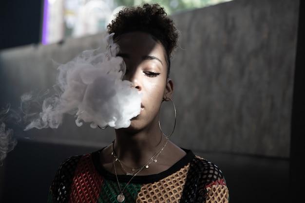 Ragazza nera con i capelli ricci e grandi orecchini che fumano con un piroscafo e soffiano un fumo profondo