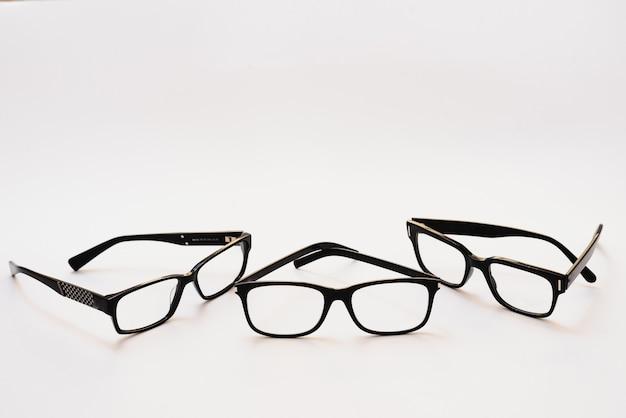 Occhiali neri su sfondo bianco, stile hipster, montature in plastica, concetto di scarsa visione
