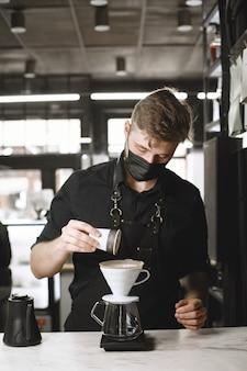 Caffè macinato nero. il barista prepara una bevanda. caffè in una brocca di vetro.
