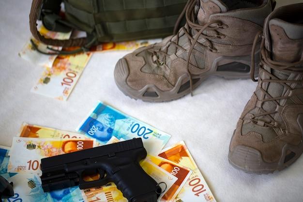 Munizioni pistola nera (pistola), un mucchio di contanti con banconote di nuovi sicli israeliani. stivali, pistola