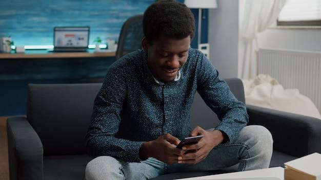 Ragazzo nero nel suo salotto che usa il telefono per navigare sui social media, connessione internet e comunicazione