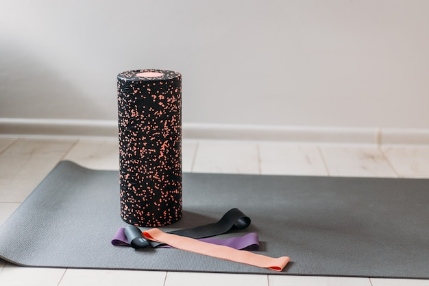 Bugia del rullo ginnico nero con elastici fitness sul pavimento di una palestra. allenamento indoor e outdoor. sport e concetto di stile di vita attivo sano.