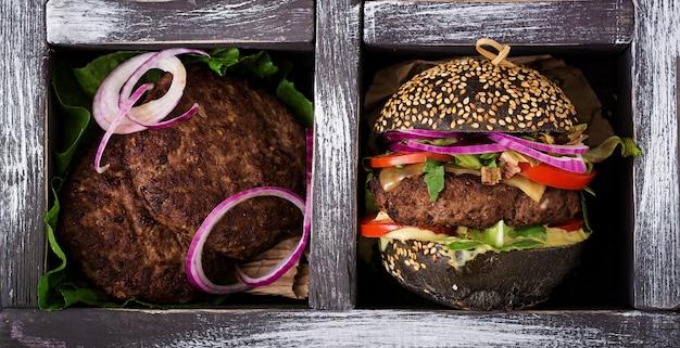 Hamburger nero con hamburger di manzo succulento, formaggio, pomodoro e cipolla rossa