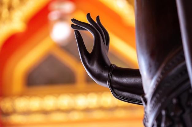 Mano nera della statua del buddha con luce gialla.