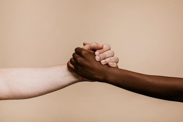 Mano nera che tiene la mano bianca